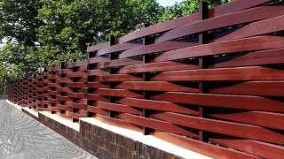 Плетеный забор на приусадебном участке. Плетение из деревянных досок и из веток березы